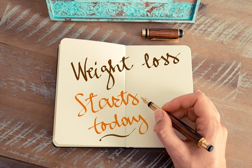 Someone writing 'Weight loss starts here' in a diary